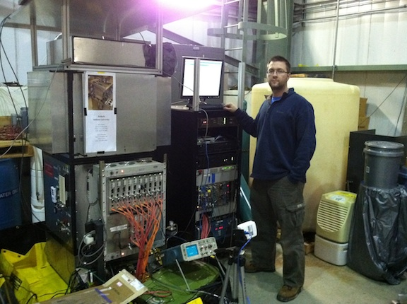An image of Dr. Robert Cooper in front of some machinery