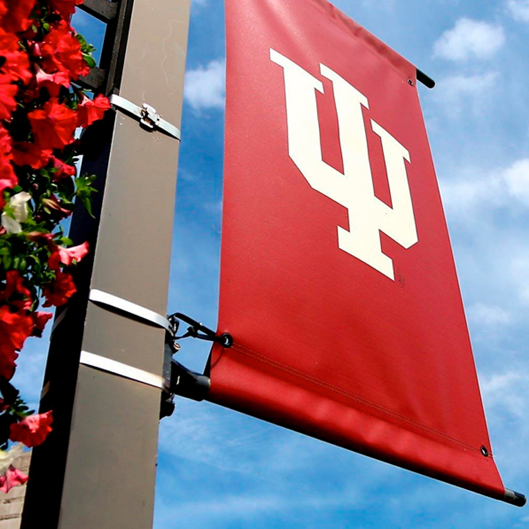 An image of an IU banner hanging above some flowers on campus.
